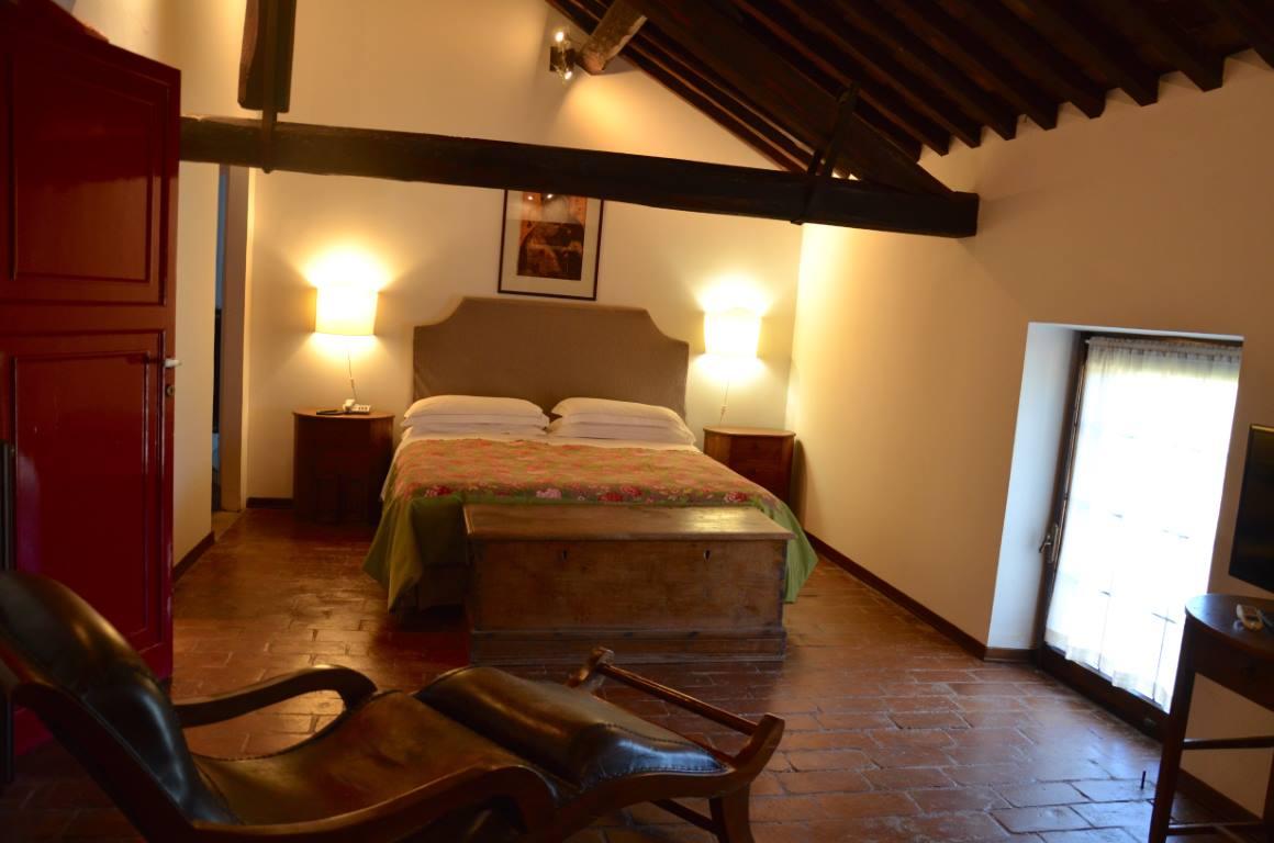 camera con trave di legno, letto e due luci laterali
